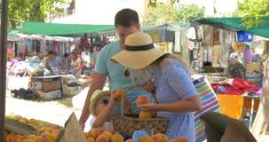 Junge Familie im Markt von Saloniki, Griechenland wählen Pfirsiche stock video