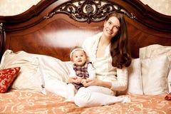 Junge Familie im Schlafzimmer Mutter und Tochter im Innenraum lizenzfreies stockbild