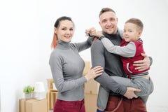 Junge Familie, Mannfrau und Kindersohn in den neuen Wohnungen Mutter hält die Schlüssel zur Wohnung Kästen mit Fracht auf a lizenzfreie stockfotografie