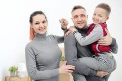 Junge Familie, Mannfrau und Kindersohn in den neuen Wohnungen Mutter hält die Schlüssel zur Wohnung Kästen mit Fracht auf a lizenzfreie stockfotos