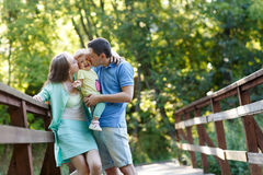 Junge Familie mit Baby im Sommerpark Stockfotos