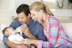 Junge Familie mit dem Baby, das auf Sofa At Home einzieht Lizenzfreies Stockfoto