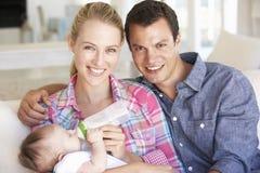 Junge Familie mit dem Baby, das auf Sofa At Home einzieht Stockfoto