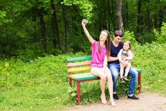 Junge Familie mit dem Kindermädchen, das draußen selfie macht stockfotografie