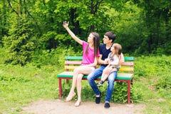 Junge Familie mit dem Kindermädchen, das draußen selfie macht stockbild