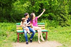 Junge Familie mit dem Kindermädchen, das draußen selfie macht lizenzfreie stockfotos