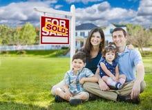 Junge Familie mit den Kindern vor kundenspezifischem Haus und für Verkaufs-Zeichen verkauft lizenzfreie stockfotografie