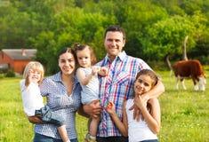 Junge Familie mit drei Kindern auf dem Bauernhof Lizenzfreie Stockbilder