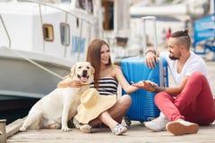 Junge Familie mit einem Hund, der für die Reise sich vorbereitet Lizenzfreies Stockbild