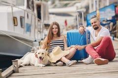 Junge Familie mit einem Hund, der für die Reise sich vorbereitet Stockbild