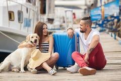 Junge Familie mit einem Hund, der für die Reise sich vorbereitet Lizenzfreies Stockfoto