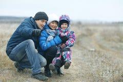 Junge Familie mit einem Kind auf Winterfeld lizenzfreie stockbilder