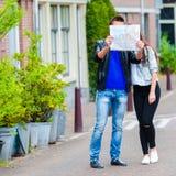 Junge Familie mit einer Karte draußen in Amsterdam Lizenzfreies Stockbild