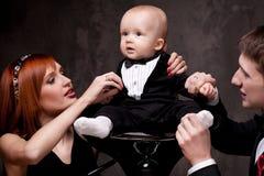 Junge Familie mit ihrem Sohn, der auf einem Stuhl sitzt Stockfoto