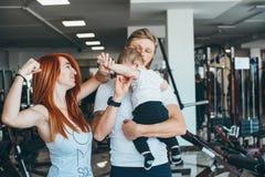Junge Familie mit kleinem Jungen in der Turnhalle stockfotografie