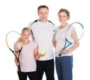 Junge Familie mit Tennis-Schlägern Stockbilder