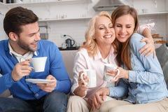 Junge Familie mit trinkendem Kaffee des Wochenendes der Schwiegermutter zu Hause stockfotografie