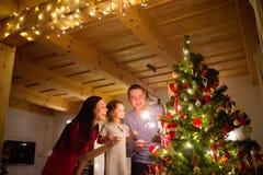 Junge Familie mit Wunderkerzen am Weihnachtsbaum zu Hause Stockfoto
