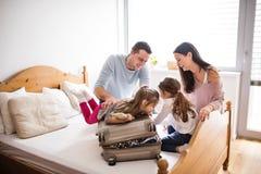 Junge Familie mit zwei Kindern, die für Feiertag verpacken lizenzfreie stockfotografie