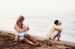 Junge Familie mit zwei Kleinkindkindern auf Strand an den Sommerferien lizenzfreie stockfotos