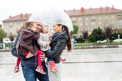 Junge Familie mit zwei Töchtern unter dem Regenschirm, Stadt Stockbild