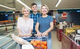 Junge Familie und ältere eine Frau, die das Einkaufen in einem supermarke tut Lizenzfreie Stockfotografie