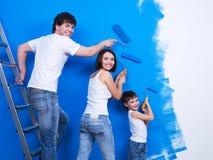 Junge Familie, welche die Wand malt Stockfotos