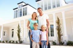 Junge Familien-stehendes äußeres Traumhaus Lizenzfreie Stockbilder