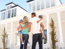 Junge Familien-stehendes äußeres Traumhaus Stockfotos