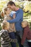 Junge Familienhaltung im Park Stockfotos