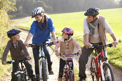 Junge Familienhaltung mit Fahrrädern im Park Stockfotos