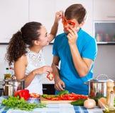 Junge Familienpaare, die Gemüse kochen Lizenzfreies Stockbild