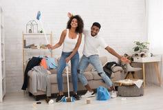 Junge Familienreinigungswohnung nach Hausparty stockfotografie