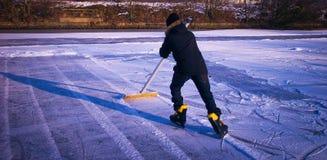 Junge fegt den Schnee vom Eis Lizenzfreie Stockfotos