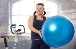 Junge fette Frau, die mit Pass-Sitzkugel trainiert Lizenzfreies Stockbild