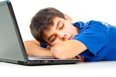 Junge fiel schlafend auf einem Laptop Stockfotos