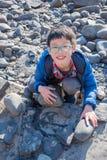 Junge finden versteinert auf dem Strand stockbild