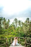 Junge Flitterwochenpaare, die tief auf der Brücke im Dschungel aufwerfen Regenwald von Bali-Insel Romantisches Trieb indonesien lizenzfreie stockfotografie