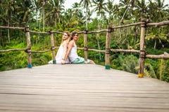 Junge Flitterwochenpaare, die tief auf der Brücke im Dschungel aufwerfen Regenwald von Bali-Insel Romantisches Trieb indonesien stockfotos