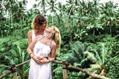 Junge Flitterwochenpaare, die tief auf der Brücke im Dschungel aufwerfen Regenwald von Bali-Insel Romantisches Trieb indonesien lizenzfreie stockbilder