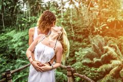 Junge Flitterwochenpaare, die tief auf der Brücke im Dschungel aufwerfen Regenwald von Bali-Insel Romantisches Trieb indonesien lizenzfreies stockfoto