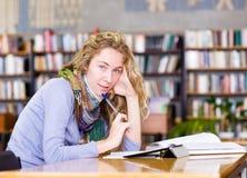 Junge fokussierten den Studenten, der einen Tablet-Computer in einer Bibliothek verwendet Lizenzfreies Stockfoto
