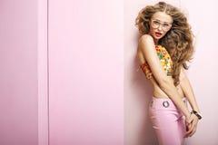 Junge formschöne Frau im rosa Raum Stockbilder