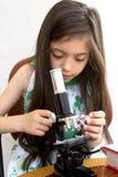Junge Forscheranalysen mit einem Mikroskop Stockbilder