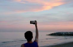 Junge fotografiert den schönen Sonnenuntergang mit einem Smartphone Lizenzfreie Stockfotografie