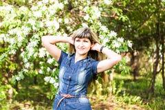 Junge Frühlingsfrau in blühendem Baum lizenzfreies stockbild