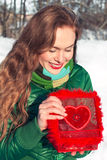 Junge Frau öffnet einen roten Kasten mit Herzen und dem Lächeln Stockbilder