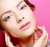 Junge Frau über rosa Hintergrund Stockbild