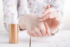 Junge Frau übergibt das Auftragen der Feuchtigkeitscreme an ihrer Haut stockfotografie