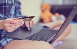 Junge Frau übergibt Kreditkarte zu Hause halten und mit Laptop arbeiten lizenzfreies stockfoto
